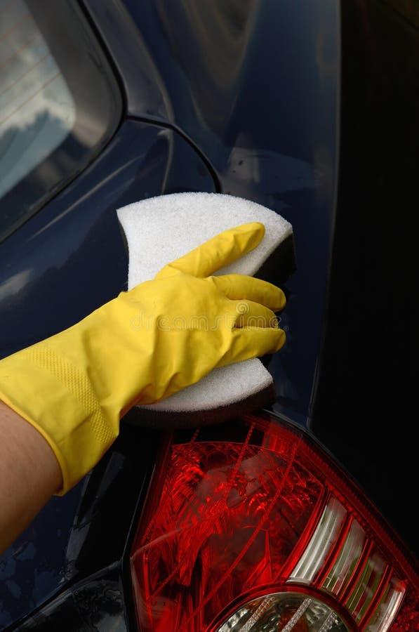 A mão em uma luva amarela lava o carro fotos de stock royalty free