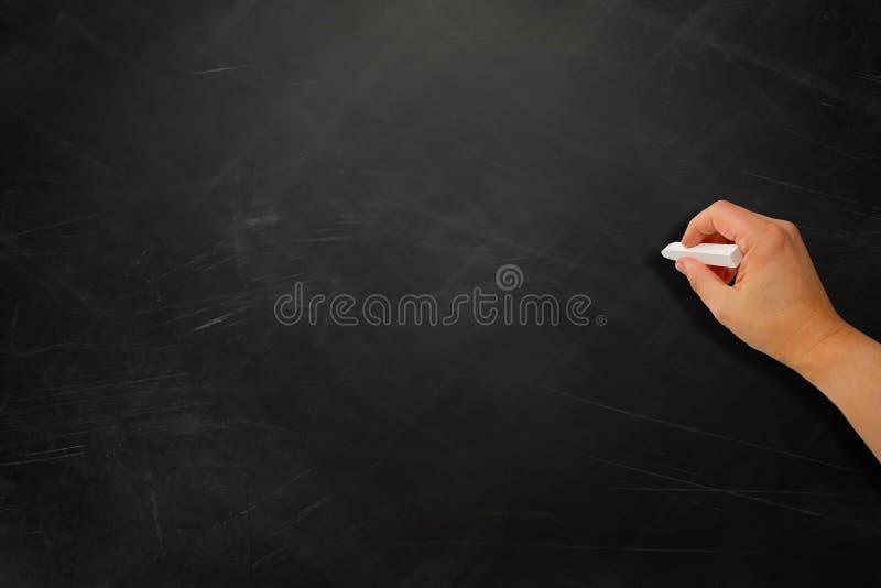 Mão em uma placa preta fotos de stock