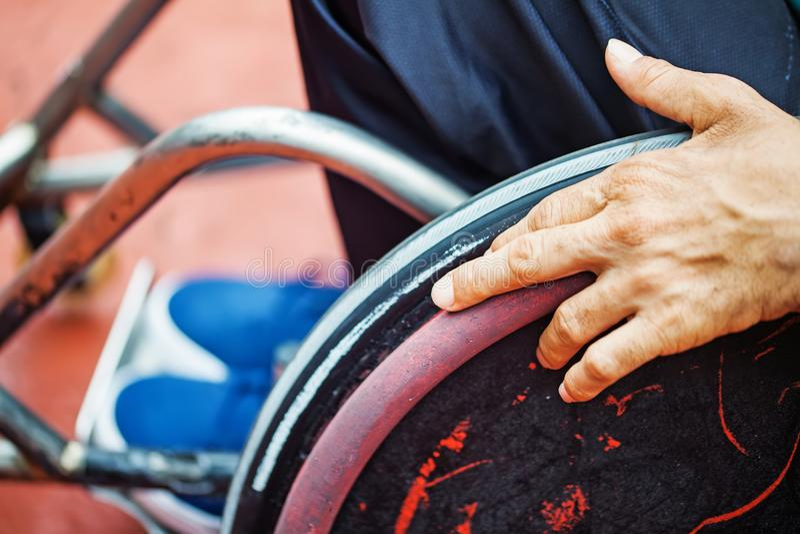 Mão em uma roda da cadeira de rodas fotos de stock