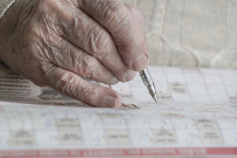 Mão enrugada que resolve o enigma fotografia de stock