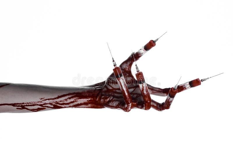Mão ensanguentado com a seringa nos dedos, seringas dos dedos do pé, seringas da mão, mão ensanguentado horrívea, tema do Dia das fotografia de stock royalty free