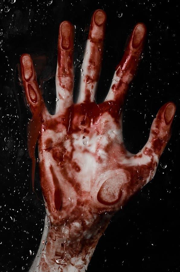 A mão ensanguentado no vidro molhado, a janela ensanguentado, uma impressão das mãos ensanguentados, zombi, demônio, assassino, h foto de stock