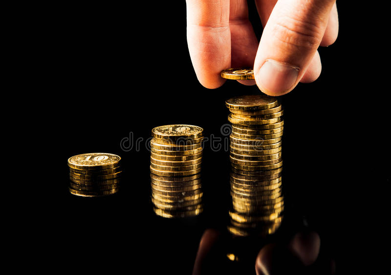 A mão entrega uma pilha de crescimento de lucro do gráfico das moedas no fundo preto imagens de stock royalty free