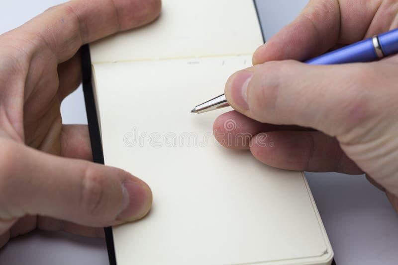 A mão escreve em um caderno foto de stock royalty free
