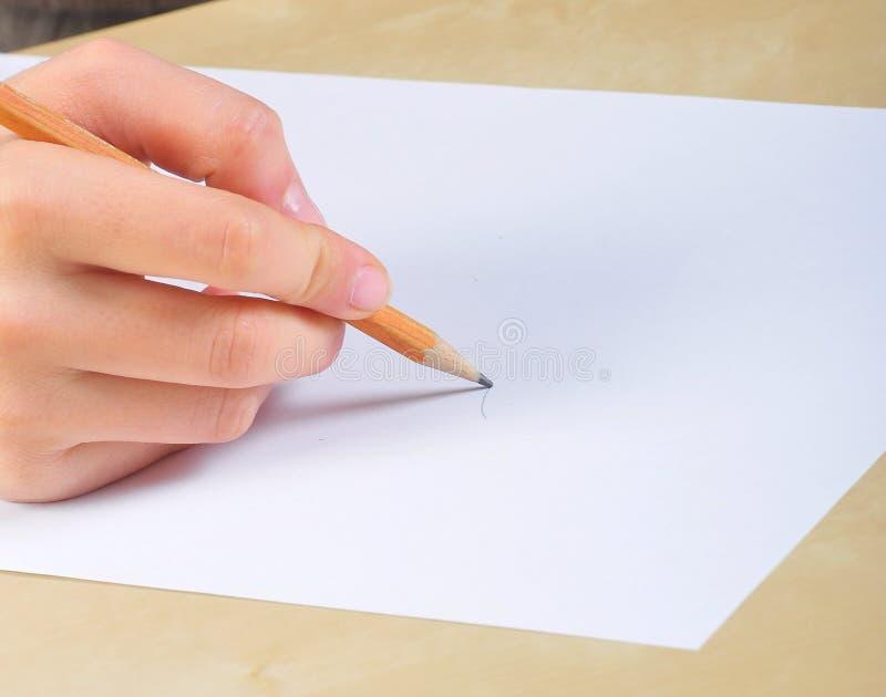 A mão escreve em um papel em branco fotos de stock