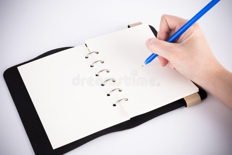 A mão escreve no caderno imagens de stock royalty free