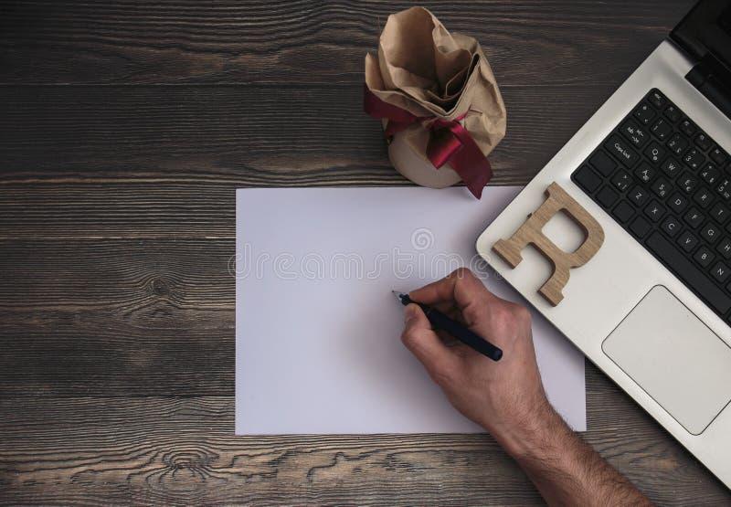A mão escreve no caderno na foto do estoque do portátil fotos de stock
