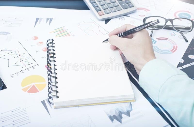 A mão escreve o caderno e documenta o gráfico financeiro na mesa imagem de stock