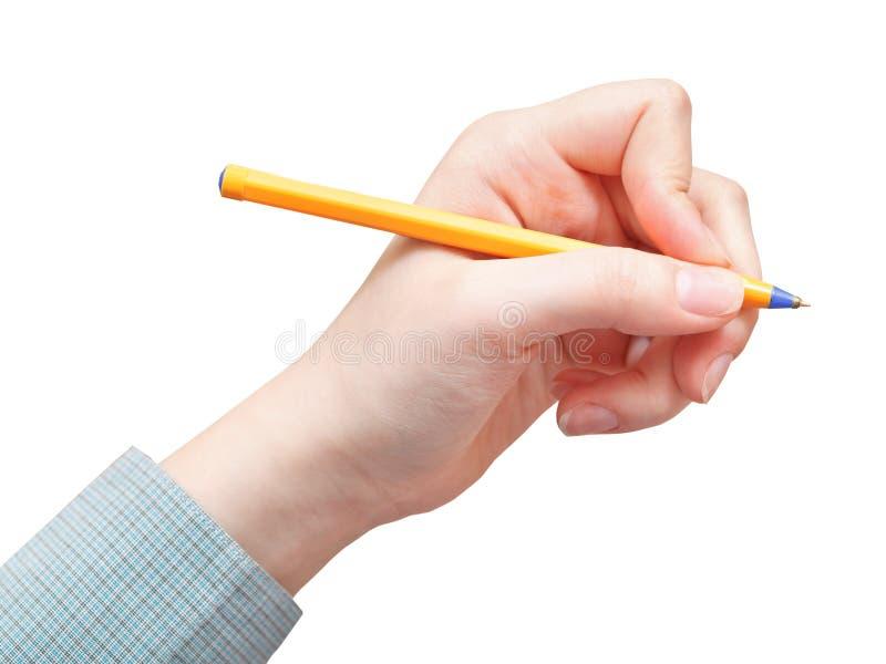 A mão escreve pela pena amarela isolada imagem de stock royalty free