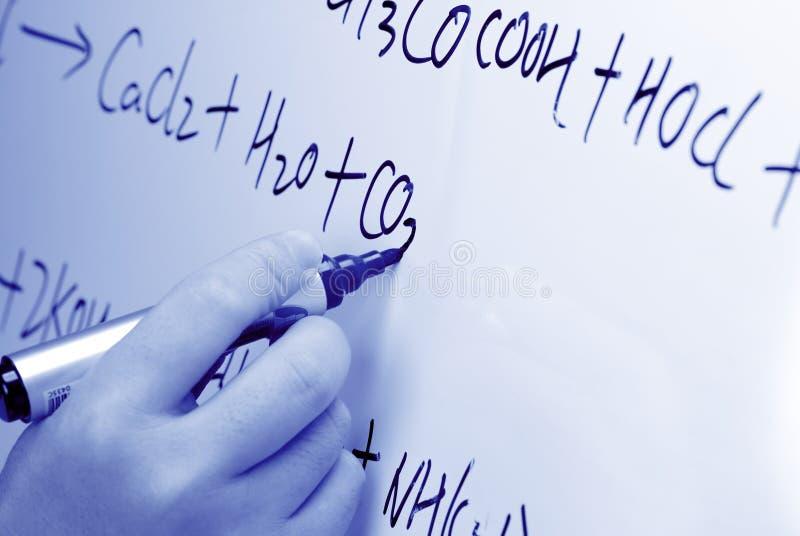 A mão escreve uma fórmula química em um whiteboard. foto de stock royalty free