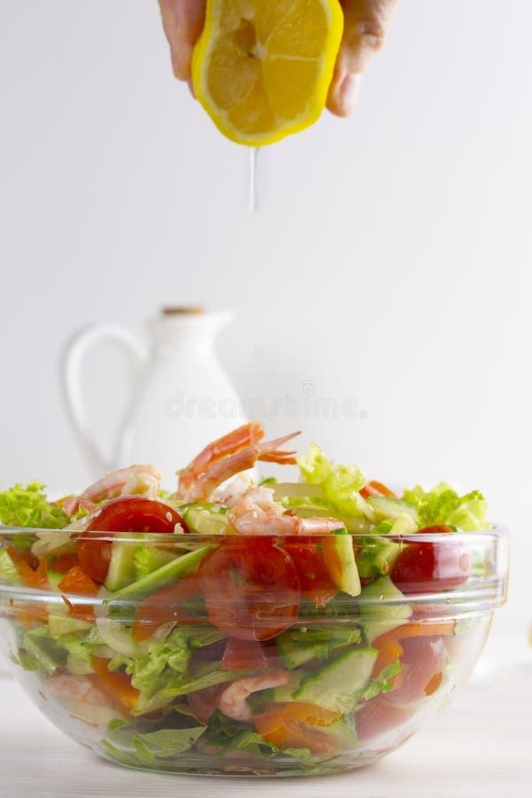 A mão espreme o suco de limão em uma salada de legumes frescos e de marisco, tomates, camarão do sésamo dos verdes dos pepinos Go fotografia de stock royalty free