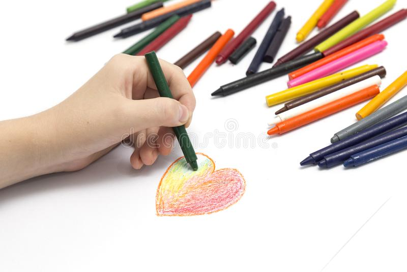 M?o esquerda que tira uma forma do cora??o com cores pastel coloridas dos past?is foto de stock