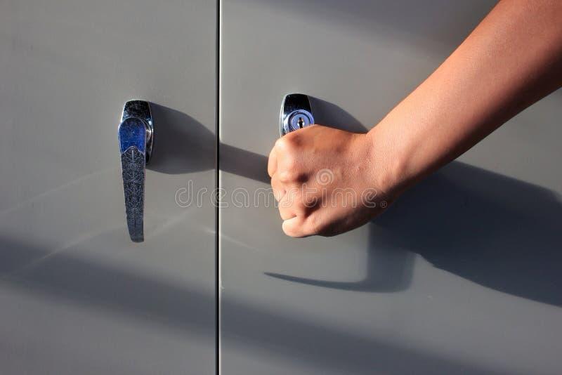 A mão está abrindo o armário de arquivo foto de stock royalty free