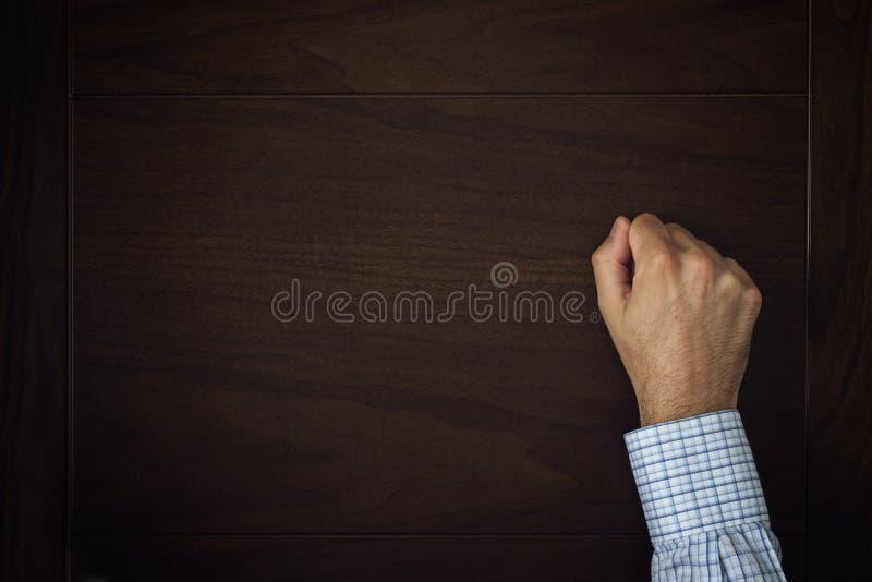 A mão está batendo na porta imagens de stock
