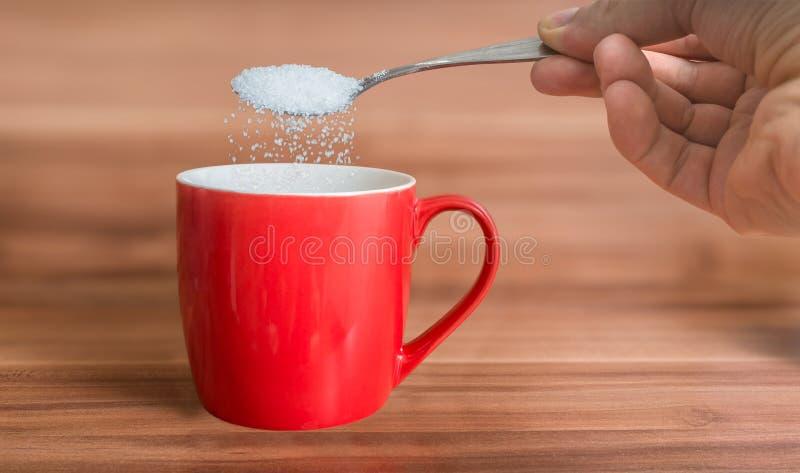 A mão está derramando o açúcar ao copo vermelho do chá Conceito insalubre comer fotos de stock