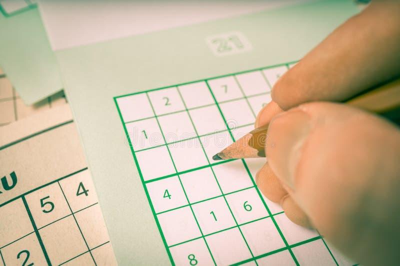 A mão está escrevendo números na grade do sudoku popular do jogo da lógica fotografia de stock