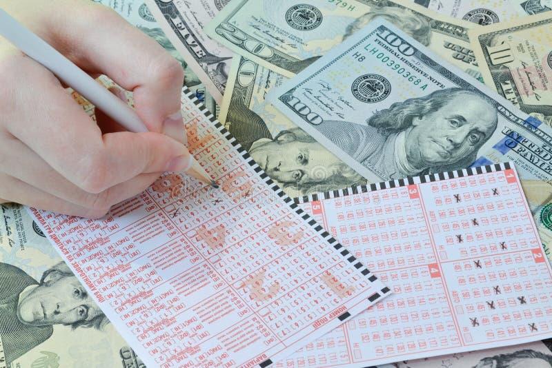A mão está escrevendo no bilhete de loteria imagens de stock