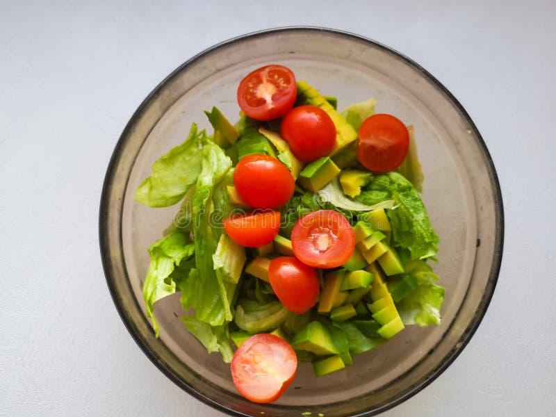 A mão está espremendo o cal sobre o vegetariano que a salada é feita do abacate, os tomates, o pepino e a manjericão fotografia de stock