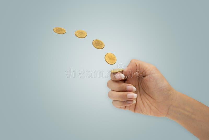 A mão está lançando uma moeda isolada no fundo azul imagem de stock