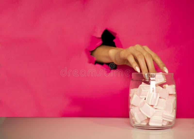 A mão está roubando o marshmallow fotografia de stock royalty free