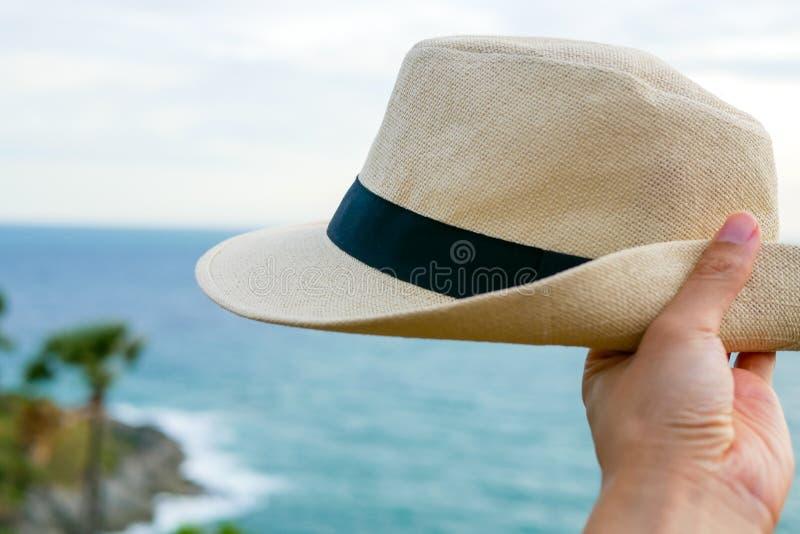 A mão estão guardando o chapéu de Panamá no mar azul e o fundo branco do céu que representam o estilo de vida do relaxamento e do imagens de stock royalty free