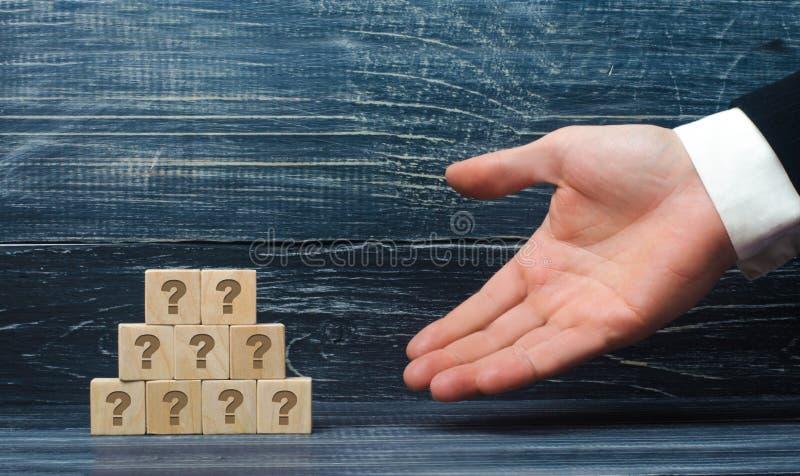 A mão estendido de um homem de negócios aponta a uma pirâmide de quadrados de madeira com os símbolos do ponto de interrogação Pr imagens de stock royalty free