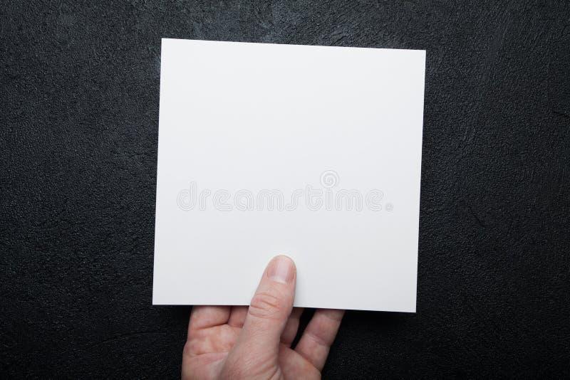 Mão europeia que guarda o papel quadrado branco Apresenta??o do folheto fotografia de stock