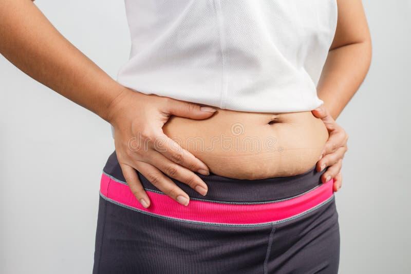 Mão excesso de peso da mulher que comprime a barriga excessiva gorda imagem de stock royalty free