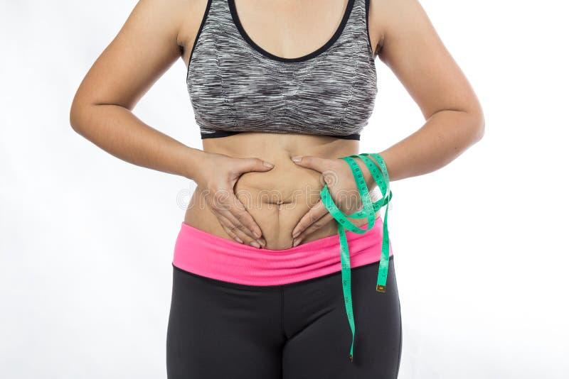 Mão excesso de peso da mulher que comprime a barriga excessiva gorda imagem de stock