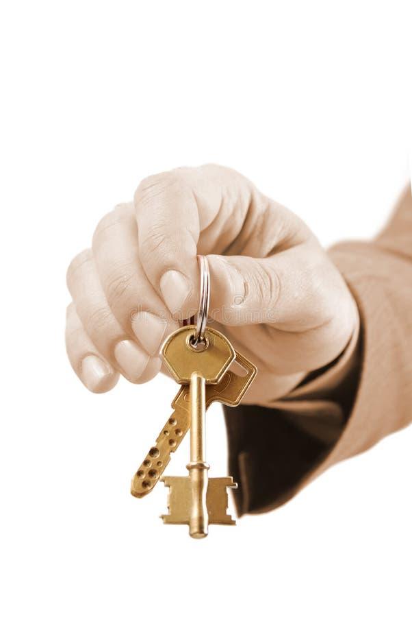 Mão executiva masculina dos bens imobiliários que prende duas chaves. fotos de stock