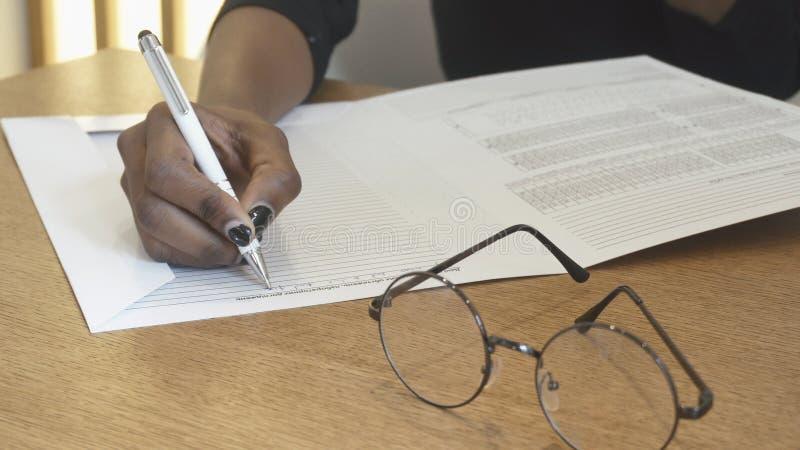 A mão fêmea africana da menina na recepção está escrevendo algo no jornal Os monóculos na mesa Não foto de stock