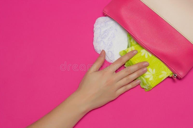 A mão fêmea alcança para a bolsa em que as almofadas sanitárias para a mentira da menstruação, fundo cor-de-rosa, espaço da cópia foto de stock royalty free