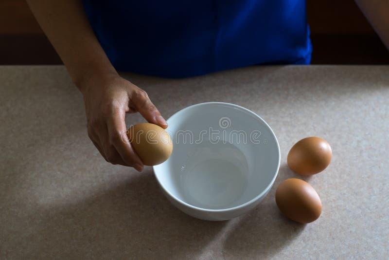 Mão fêmea asiática que guarda o ovo da galinha fotos de stock royalty free