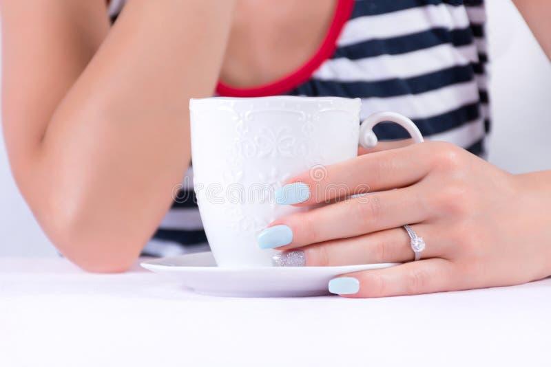 Mão fêmea bonita com a aliança de casamento do diamante e o tratamento de mãos azul do polimento de pregos que guardam a xícara d imagens de stock royalty free