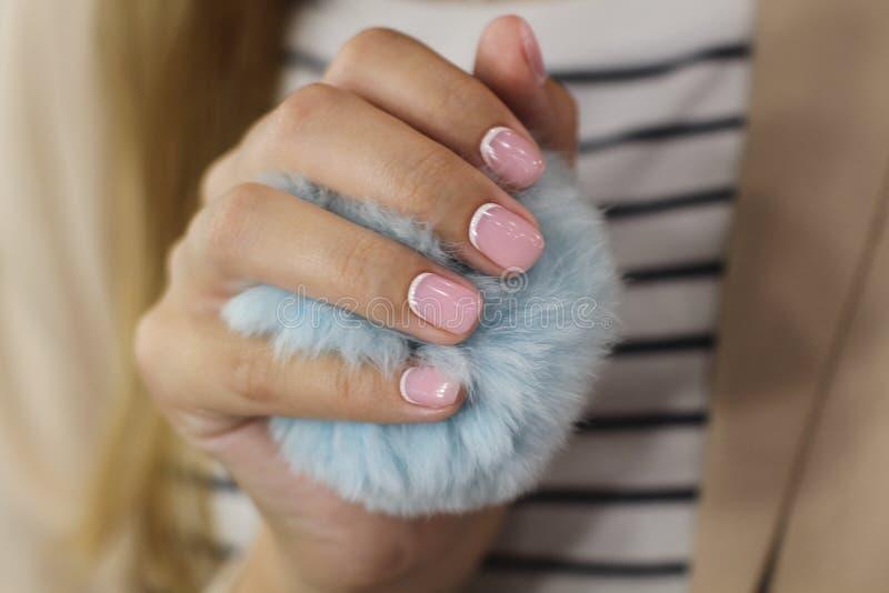 A mão fêmea bonita com tratamento de mãos guarda uma bola macia azul Verniz para as unhas cor-de-rosa delicado com crescentsand b foto de stock royalty free