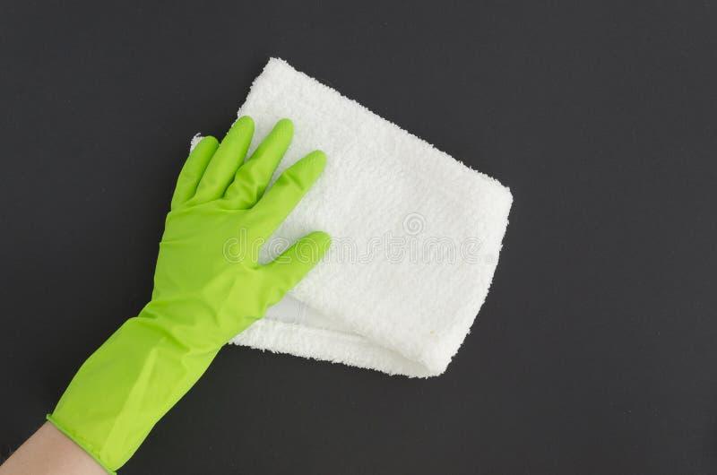 Mão fêmea colocada plano na luva verde do látex com o pano de limpeza no fundo preto Zombaria acima Copie o espaço fotos de stock royalty free