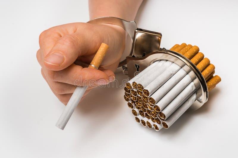 Mão fêmea com algemas e cigarros no branco foto de stock royalty free