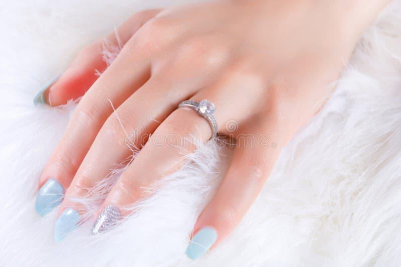 A mão fêmea com aliança de casamento do acoplamento do diamante e os pregos azuis lustram no casaco de pele branco imagens de stock royalty free