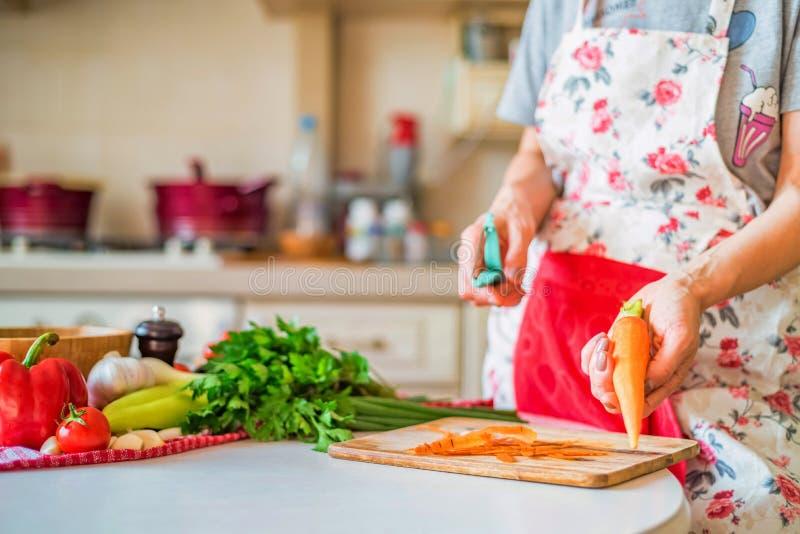 Mão fêmea com a cenoura das cascas na placa de madeira na cozinha Cozinhando vegetais fotos de stock royalty free