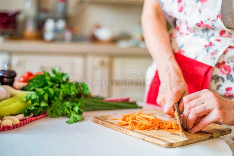 Mão fêmea com a cenoura das costeletas da faca na cozinha Cozinhando vegetais fotos de stock