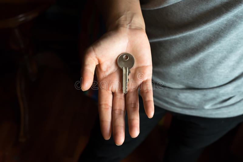 Mão fêmea com chave na palma foto de stock royalty free
