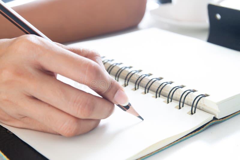 A m?o f?mea com escrita do l?pis no caderno, fecha-se acima do tiro imagem de stock