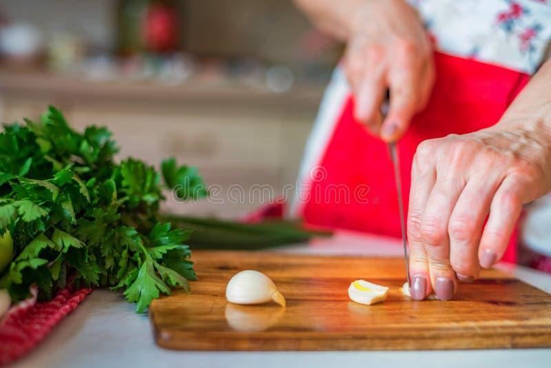 A mão fêmea com faca desbasta o alho na cozinha Cozinhando vegetais foto de stock