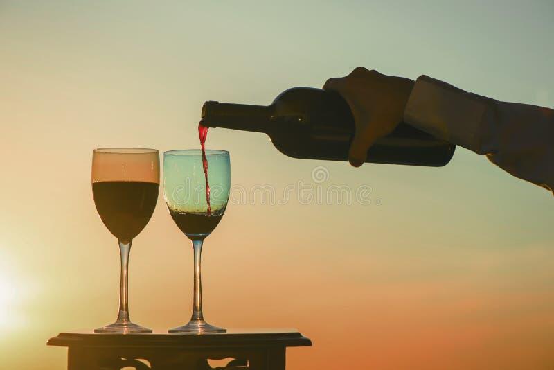 A mão fêmea com garrafa derrama o vinho tinto em vidros em um fundo do por do sol fotografia de stock