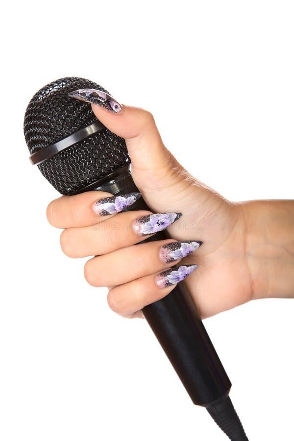 A mão fêmea com manicure prende o microfone foto de stock royalty free