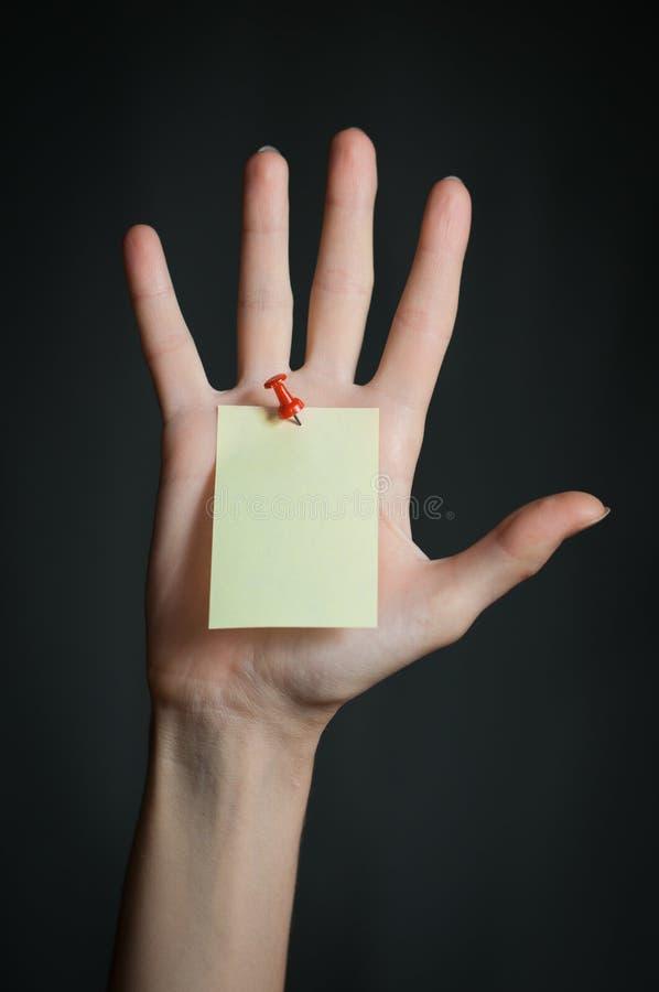 Mão fêmea com nota em branco imagem de stock
