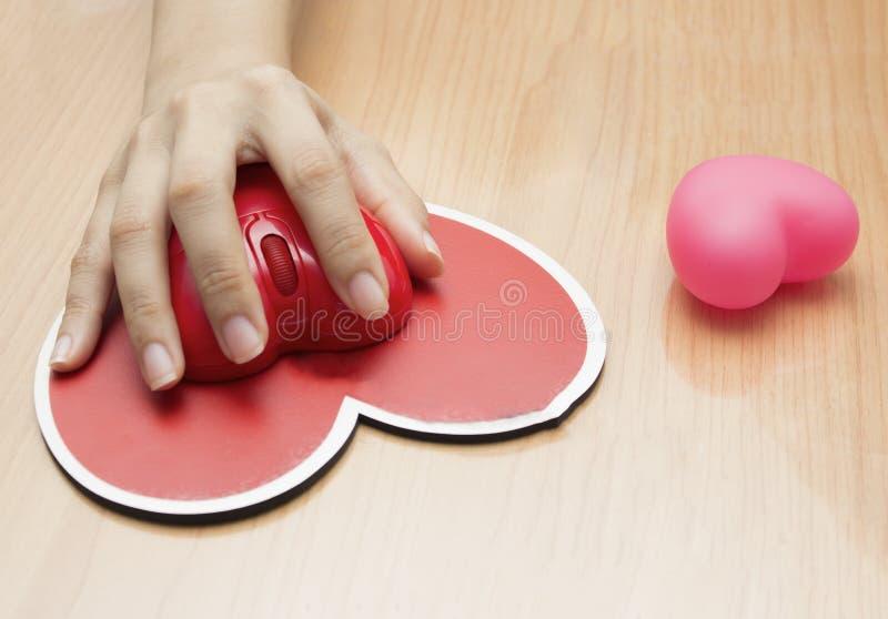 Mão fêmea com o rato do computador na tabela Dia do Valentim imagem de stock