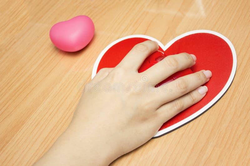 Mão fêmea com o rato do computador na tabela Dia do Valentim imagem de stock royalty free