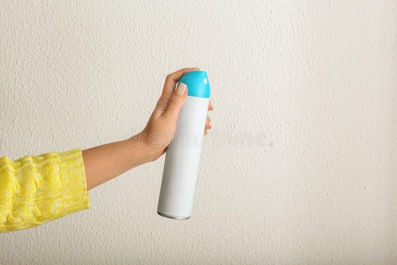 Mão fêmea com o refrogerador de ar no fundo claro foto de stock