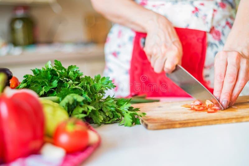 Mão fêmea com o tomate das costeletas da faca na cozinha Cozinhando vegetais fotografia de stock